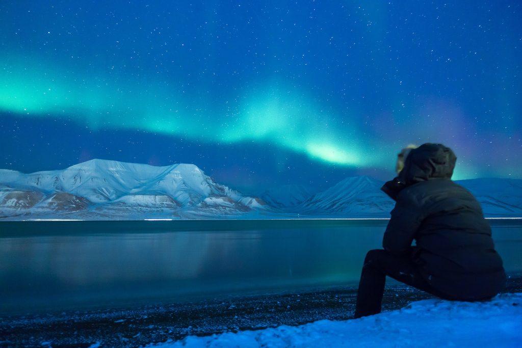 voyageur en Alaska admirant le spectacle d'une aurore boréale bleue